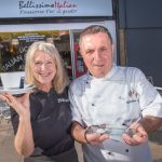 Bellissimo chef and manager holds award outside cafe