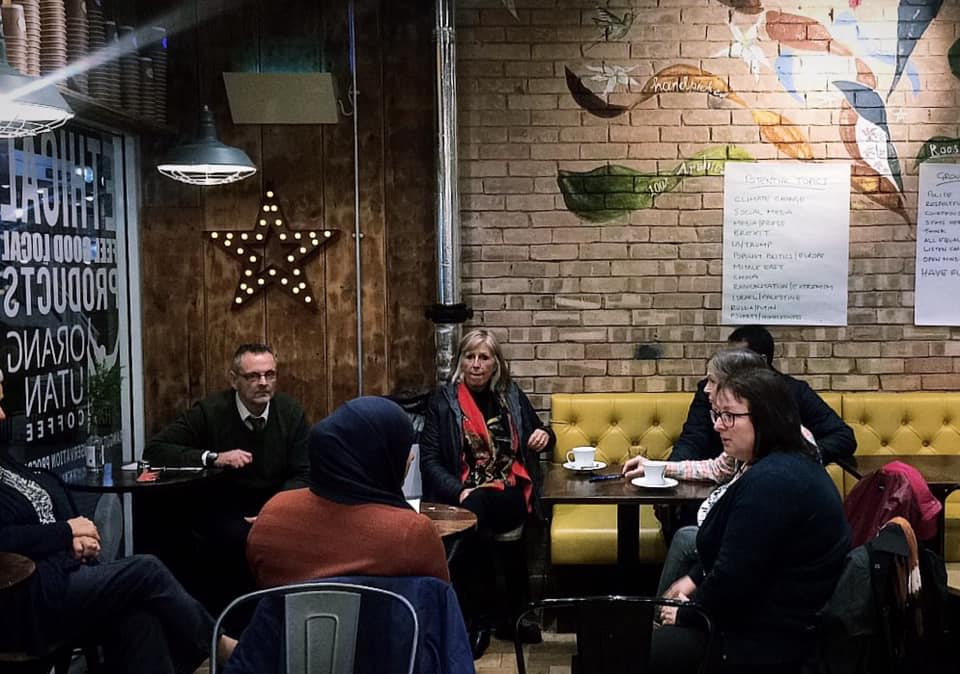 Diverse mix of coffee drinkers discussing issues