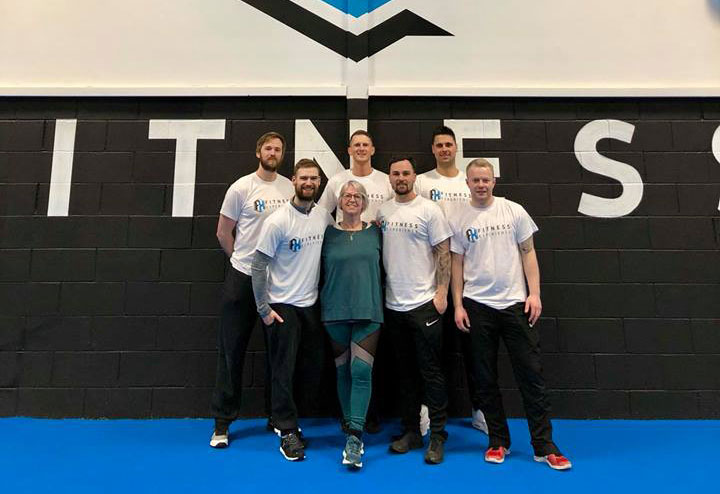 Seven FX Fitness employees smiling in front of gym wall