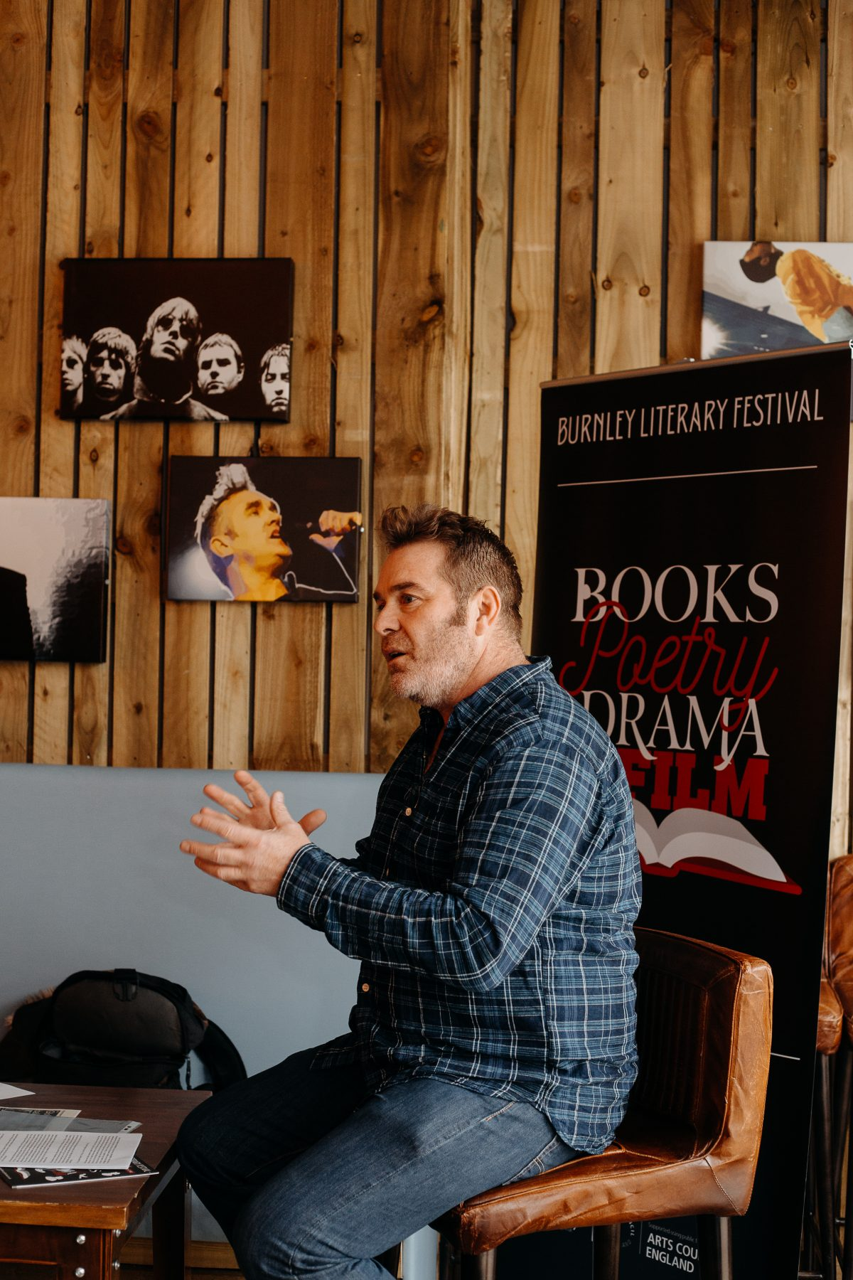 Man talking about books in front of literary festival banner
