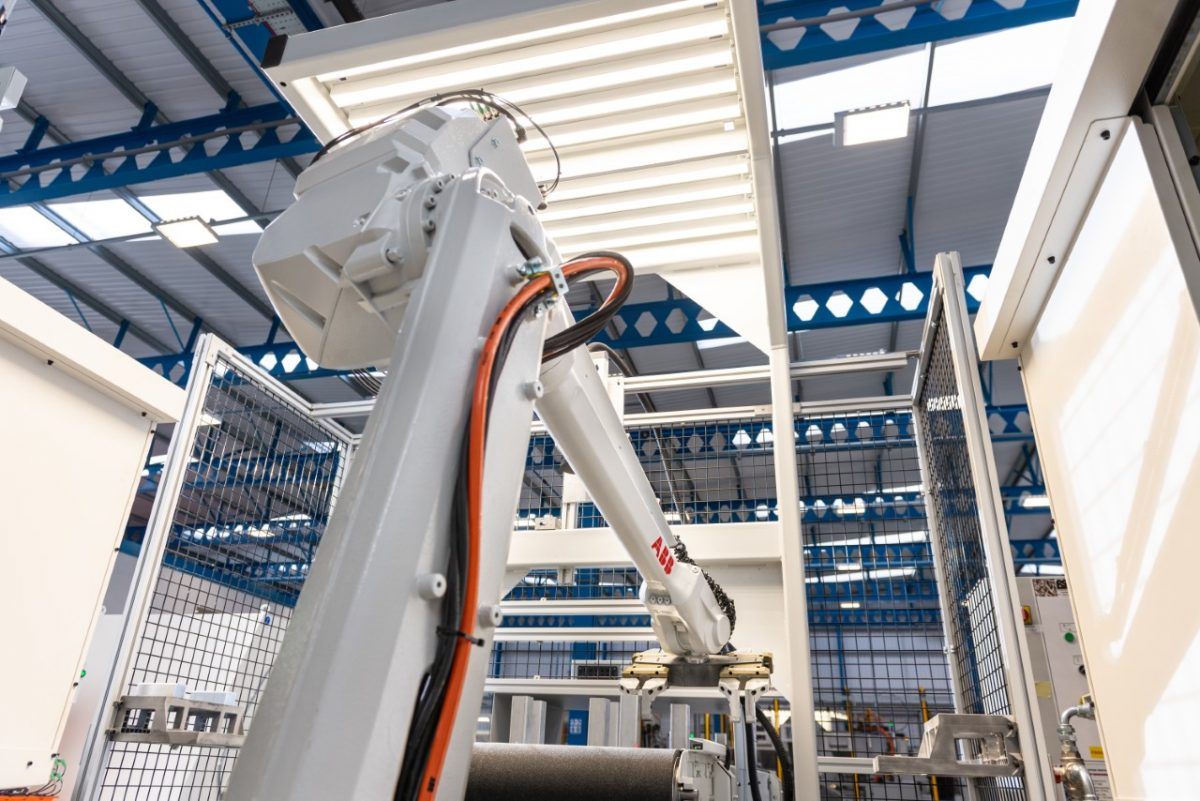 White modern robotic arm picking up a product