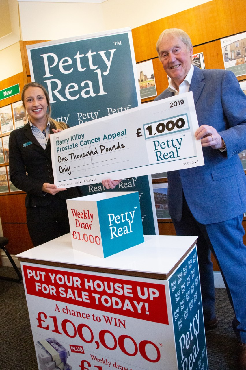 barry kilby with petty real holding up large cheque