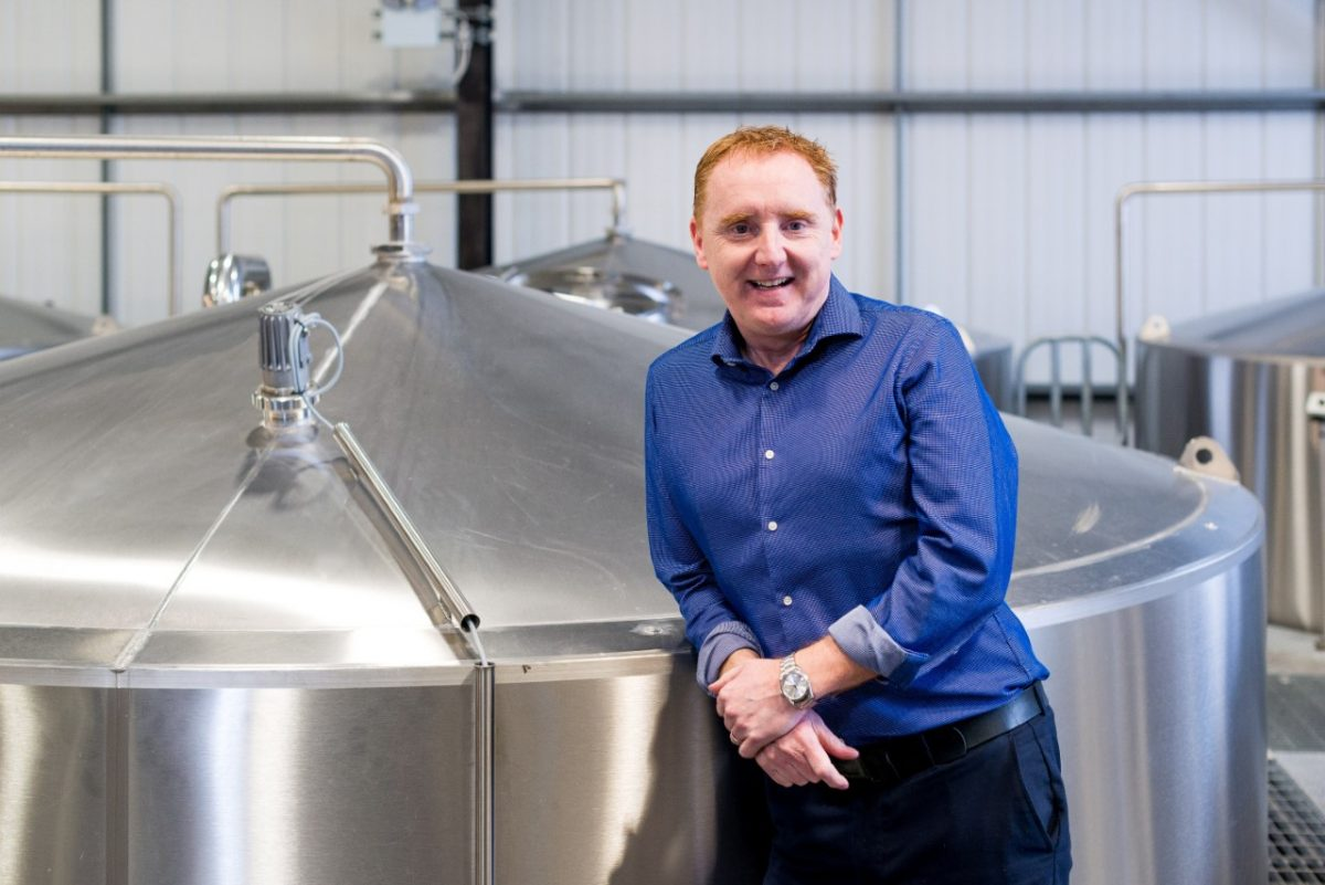 Man standing next to brewing silo