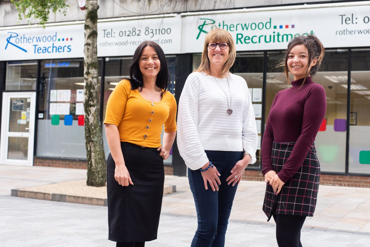 Three Rotherwood employees in front of shops