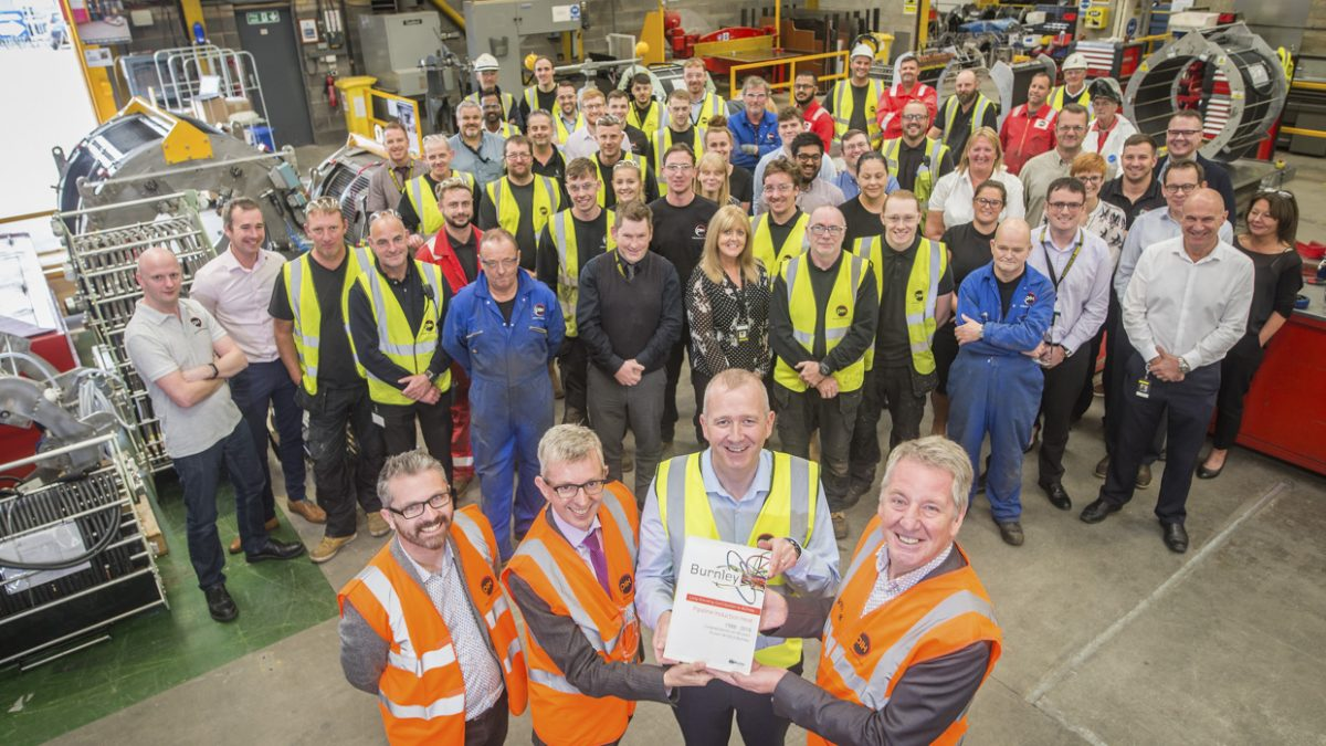 Factory bosses and staff pose with a bondholder certificate