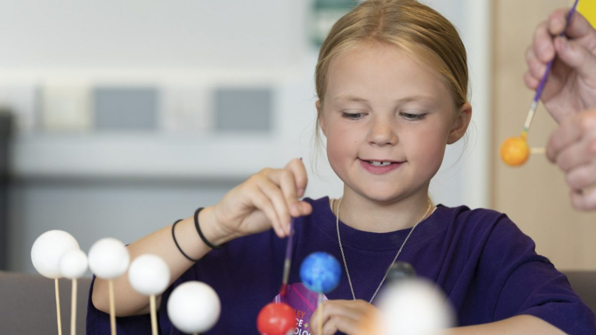 A primary school child making a model of the solar system, painting planets